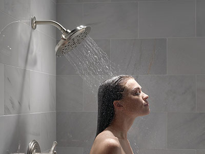 Woman taking a saturating shower using UltraSoak Spray shower head