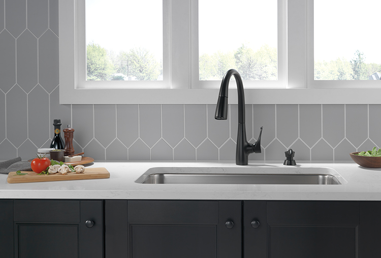 Matte black pull-down kitchen faucet against geometric wall design