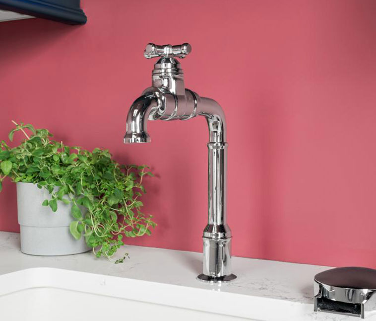 Broderick bar faucet shown on white sink against dark coral wall