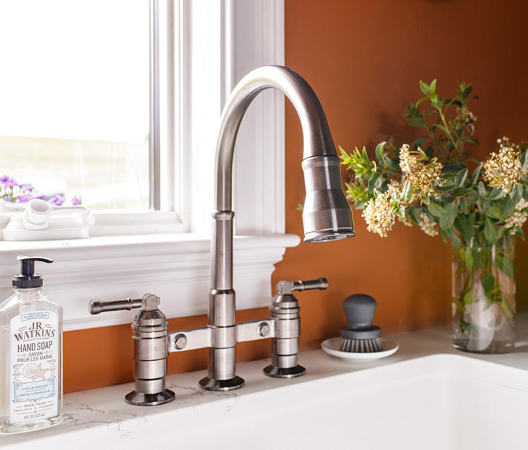 Broderick bridge kitchen faucet over white sink with displaying flowers