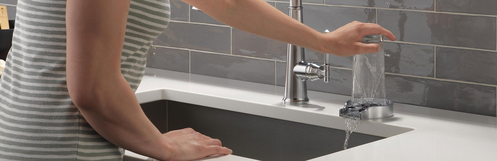 Woman using glass rinser on white countertop with grey brick wall