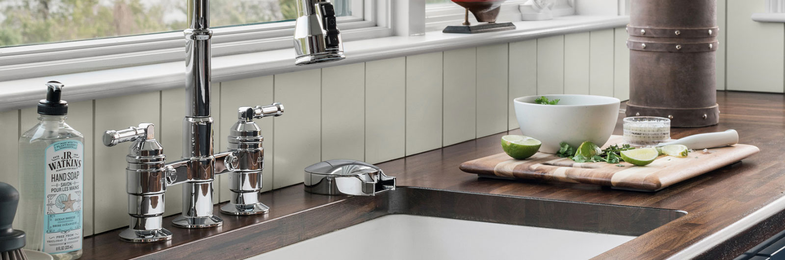 Chrome glass rinser on the right side of sink in classy kitchen