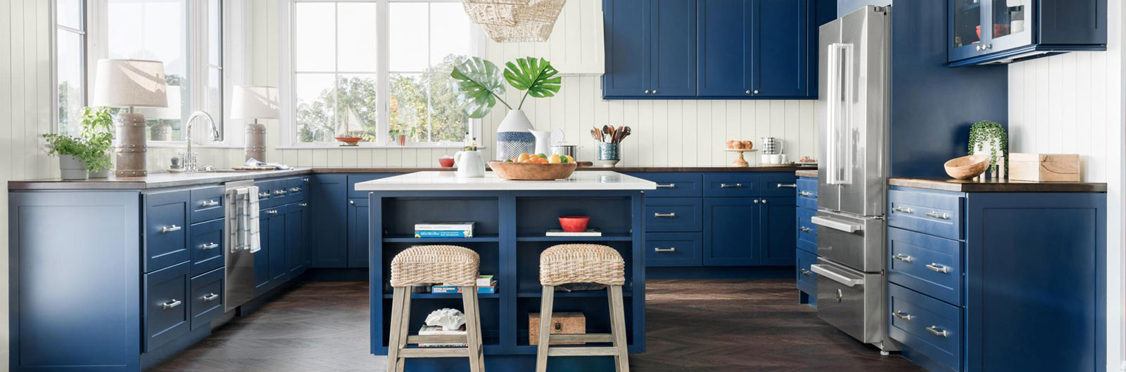 Wide shot of chic kitchen with moody blue cabinets and white walls