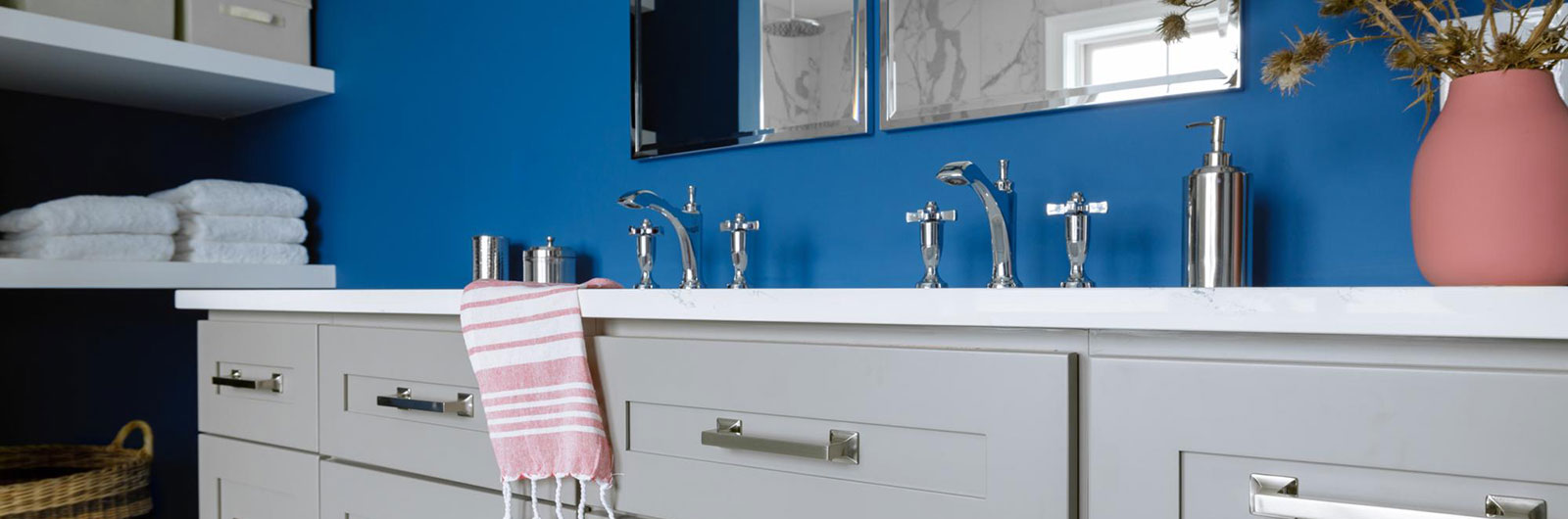Two modern, chrome bathroom faucets on double sink vanity with dark sky blue wall
